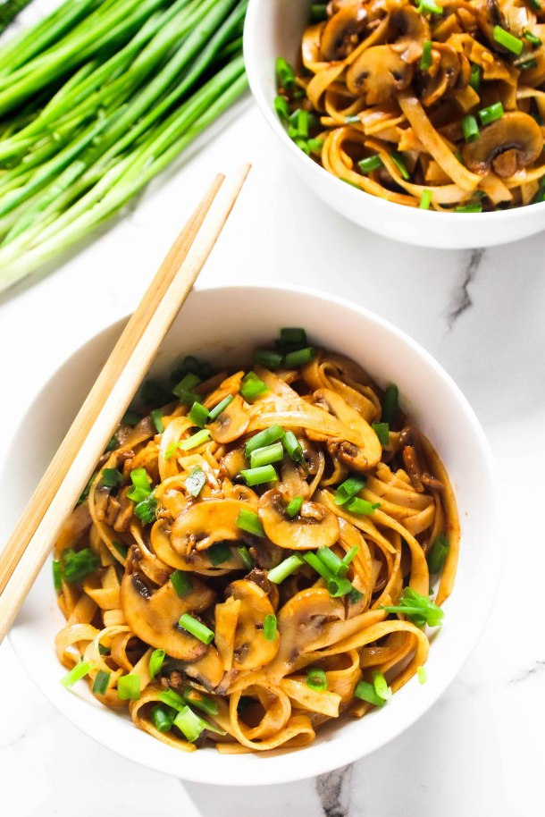 Rice Noodles topped with mushrooms and green spring onions (Scallions) in a white bowl with chopsticks placed on them. Placed on a white tile.