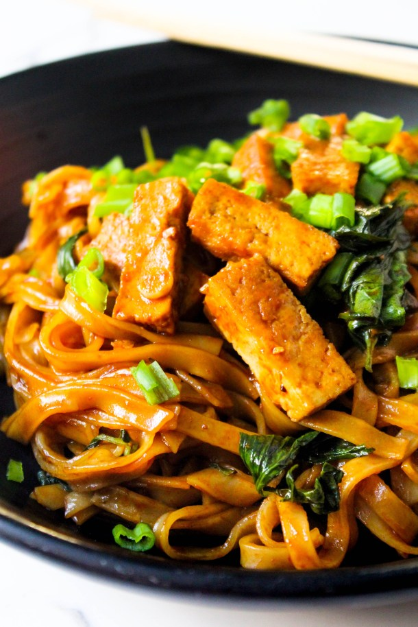 Red Brown Rice noodles coated in a vegan sauce mixed with basil and topped with crunchy tofu strips, served in a black dish placed on a white tile.