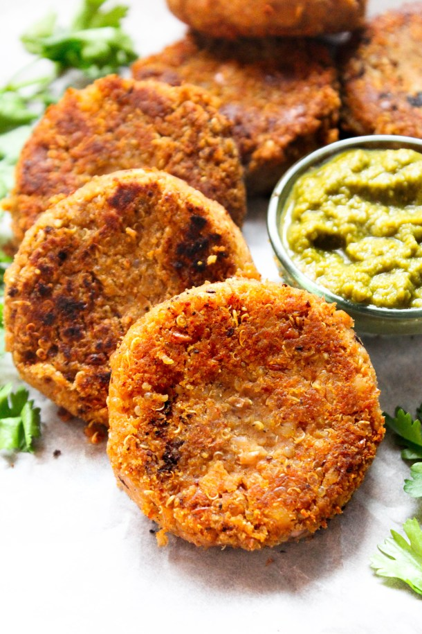 Reddish brown circular kebabs or fritters made of red kidney beans and quinoa. Served with green coriander chutney. Placed on a white tile.