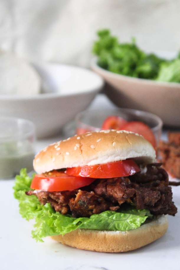 Onion Pakoda Burger (stacked with brown pakodas, slices of tomatoes, fresh lettuce leaves) placed on a white tile.