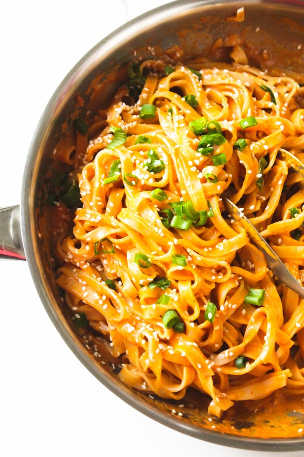 Creamy vegan thai red curry paste rice noodles in a pan. Topped with sesame seeds and green spring onions.