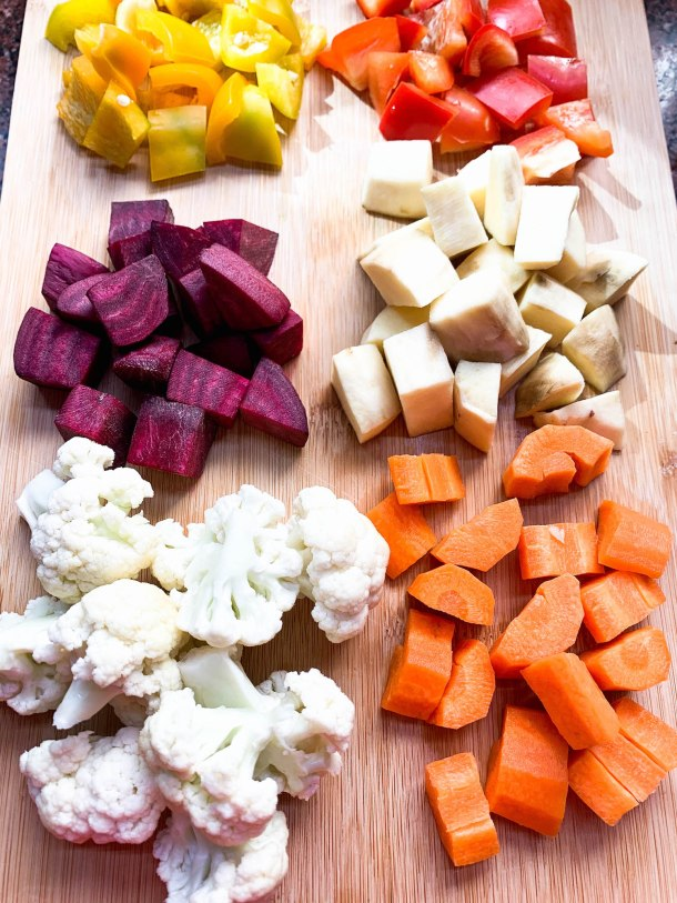 Beetroot hummus spread on a white bowl topped with roasted carrots, peppers, beets, cauliflower and sweet potato.