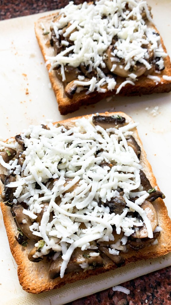 Mushrooms, cheese and garlic on toasted bread placed on white chopping board.