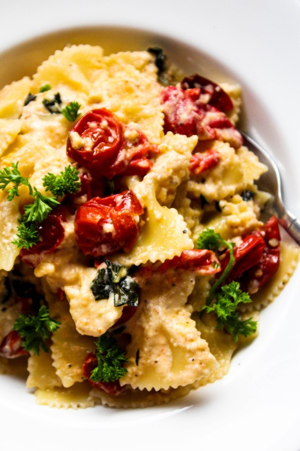 Baked Feta cheese pasta (farfalle) with cherry tomatoes and basil in a white bowl on a white tile.