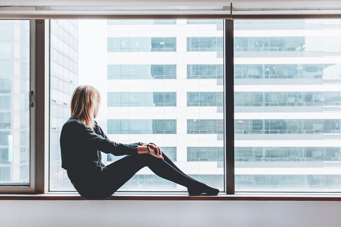 woman sitting in a large window, looking out at an office window