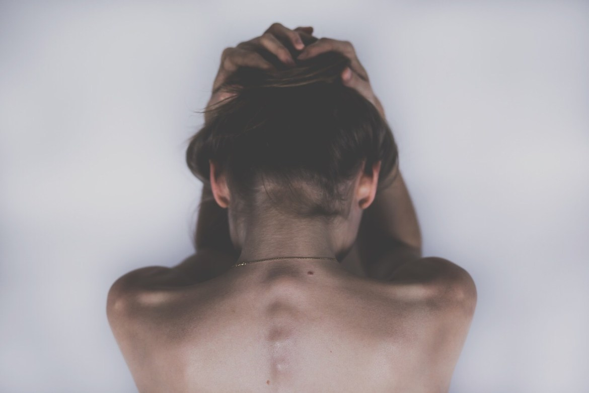a view of a woman from the shoulders up , seen from behind, cradling her head in her hands