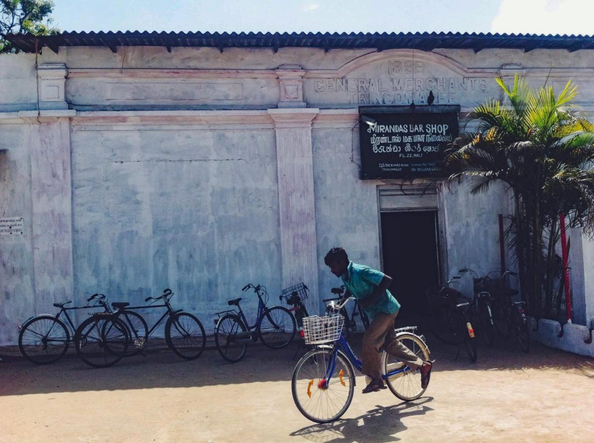 Guy on bike by Sri Lankan liquor store