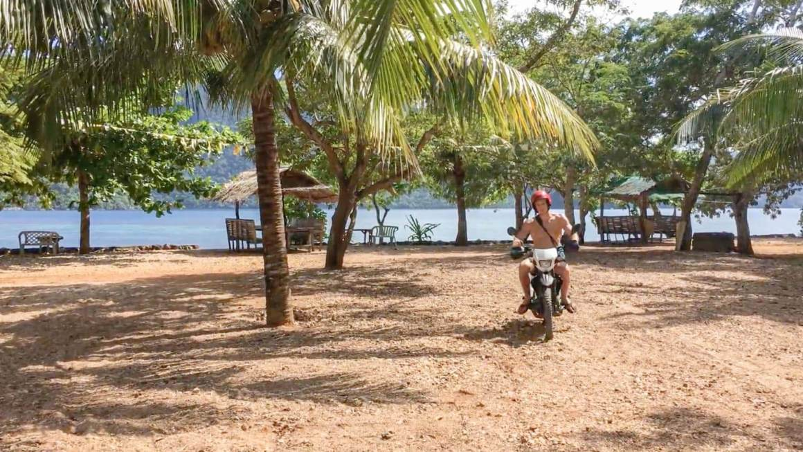 Chris riding a motorcycle by the beach with Coron Island in background