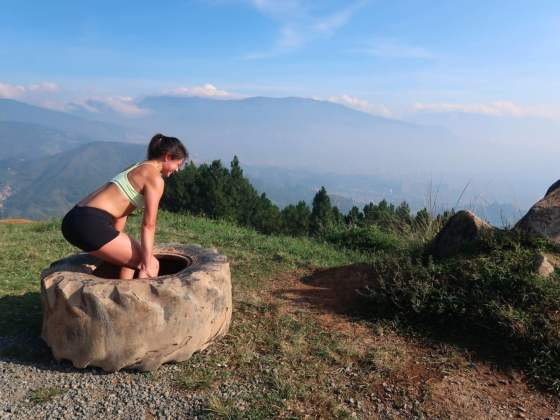 kim deadlifting a tire at the top of cerro las tres cruces medellin colombia