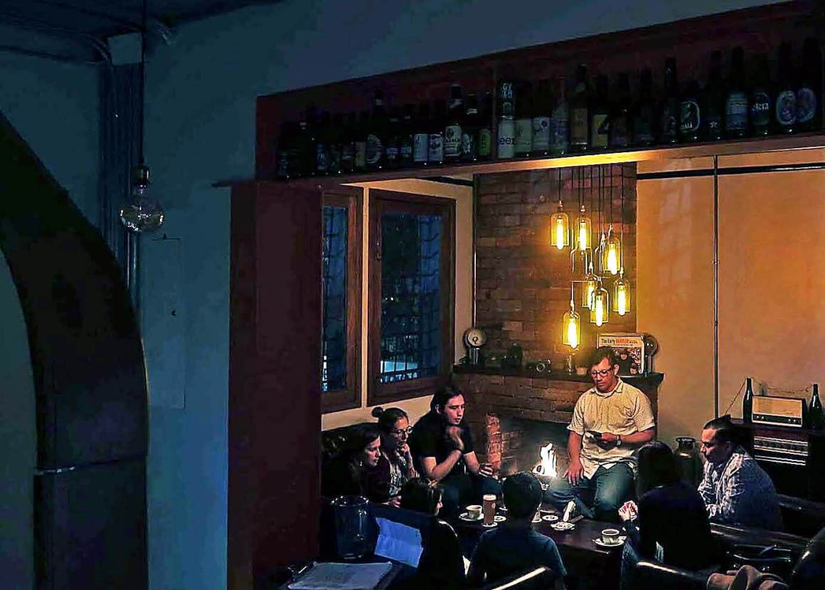 People sitting around a table and fireplace in Origen Brewery in Bogota.