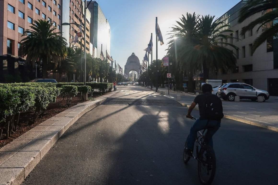 Guy biking down street towards Monumento a la Revolucion