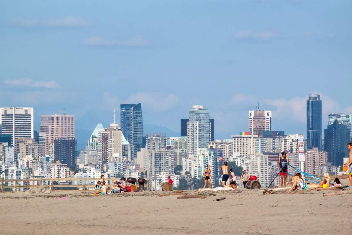 cover photo for cool things to do in vancouver of locarno beach with downtown vancouver behind it