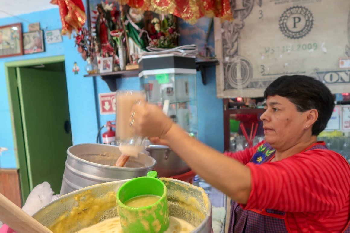 Serving pouring pulque curado from big tubs