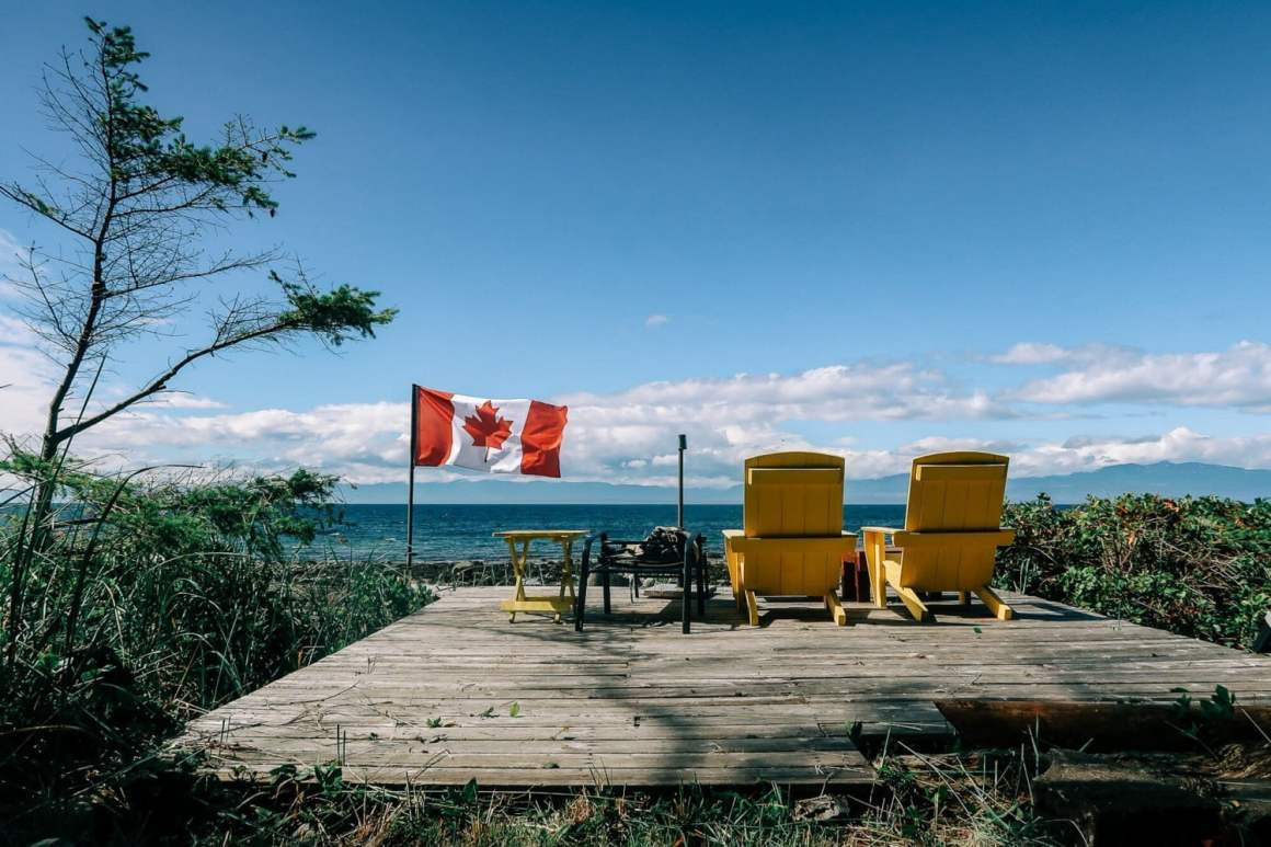 Cover image for the Savary Island travel guide: A pair of deck chairs on the beach with a flapping Canadian flag.