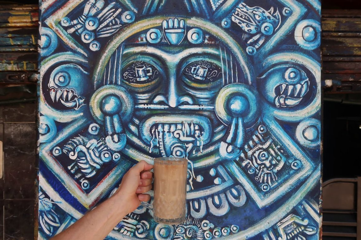 Wall painting at a Mexico City pulqueria with someone holding a mug of pulque below it