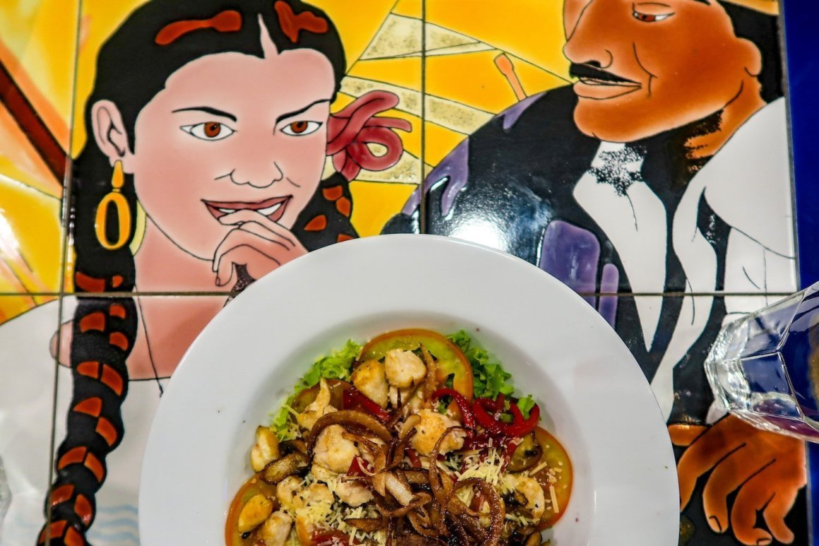 Cover image of best restaurants in Medellin post - a colorfully painted table and a plate of food