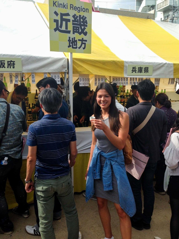 kim looking happy with sake inside festival grounds saijo sake festival