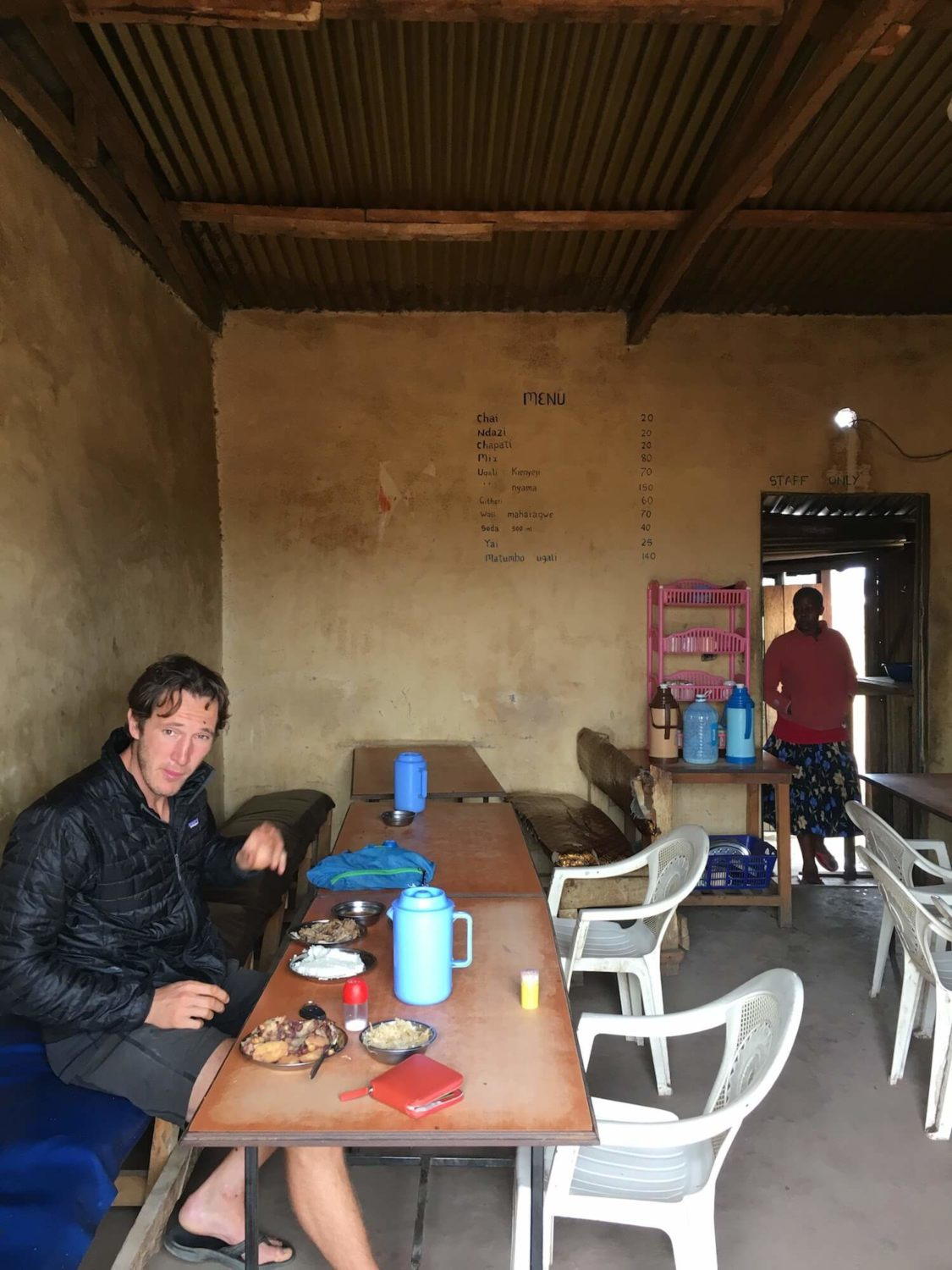 Chris eating a meal in a shack in Kenya