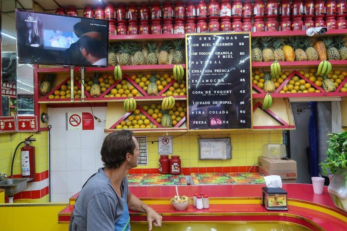 Chris reading menu at Jugos Canada in Mexico City