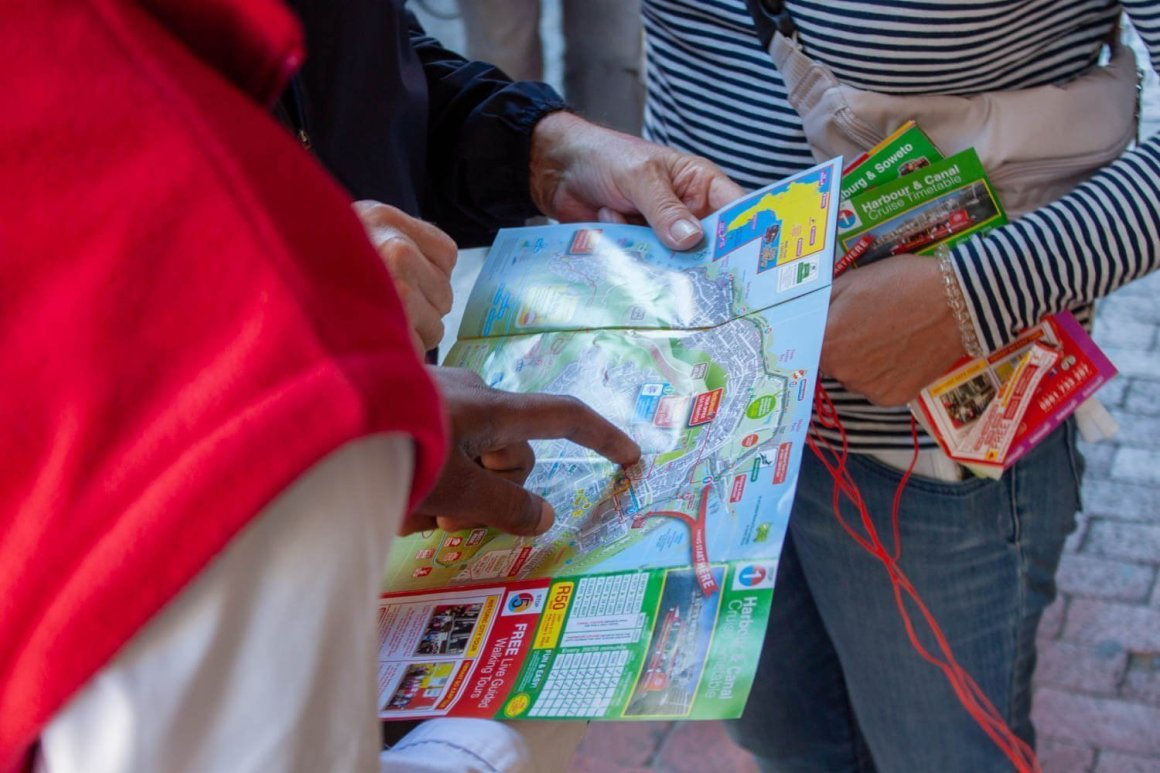 Driving looking at map with tourists