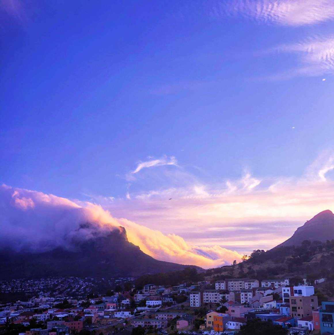 View from Bo Kaap of clouds over Table Mountain at sunset.