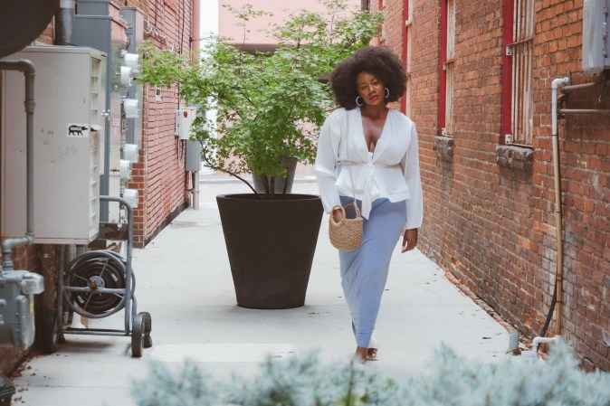 Black woman in white blouse and blue skirt walking.