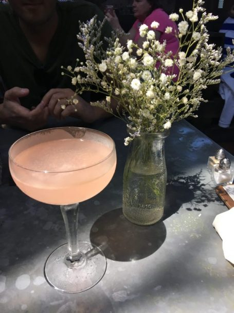 Ice Plant Bar Pink Cocktail next to white flowers