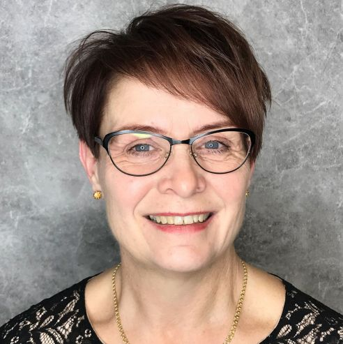 Pixie-Crop-with-Asymmetrical-Bangs 10 Flattering and Stylish Hairstyles for Women over 50 with Glasses