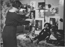 "The famous clown ""Grock"" back in Berlin. The lady who is decorating his dressing room with photographs is Mrs. Grock. 306-NT-290-MM-2. Source: Wide World Photos (Potential copyright restrictions)."