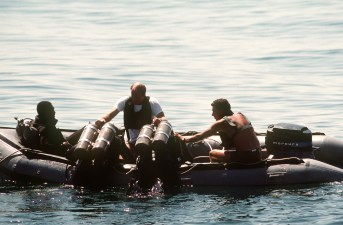 330-CFD-DN-ST-88-04245: US Navy divers are helped aboard an inflatable boat by fellow divers during recovery operations for the space shuttle Challenger.