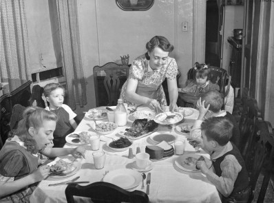 A New York, N.Y. mother serves a meal planned to provide the vitamins and minerals that will build better minds and better bodies in six future citizens of the United States. Forsythe. Nov., 1941 (16-G-175-2-N-3109)