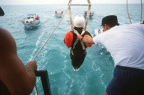 """Astronaut Sally Ride drops from a 15 foot high boat platform into Biscayne Bay during an Air Training Command """"Drop-and-Drag"""" Exercise. The boat will pull Ride through the water until she can stabilize herself and release the parachute risers. The exercise is designed to simulate being dragged through the water by a parachute."""