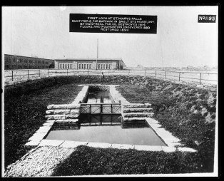 "Image shows a fenced off area around an old lock, about the size of a private swimming pool. Label on the photograph reads, ""First Lock at St. Marys Falls. Built 1797-8, for bateaux in Sault Ste. Marie, Ontario by Montreal Fur Co. Destroyed 1814. Floors and foundation uncovered 1889, restored 1890."""