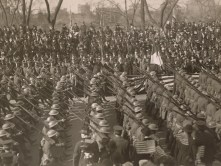Members of the 369th pass the reviewing stand during the Harlem Victory Parade. In the stand were New York Governor Al Smith, Former NY Governor Chas. S. Whitman, Rodman Wanamaker, Major General Barry, and acting mayor Moran Admiral Gleaves. Local Identifier, 165-WW-127-25.