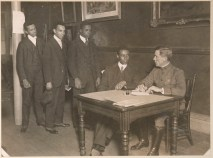 African American men enlisting at the Colored Y.M.C.A. for the Negro Officers' Training Camp at Fort Des Moines, IA. A. Merrill Willis (sitting) was the first to enlist. Local Identifier, 165-WW-127-121.