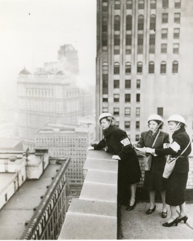 """From their observation posts on a downtown Detroit office building, these three women fire watchers study the roofs of surrounding buildings which are in their care. The women, members of the only OCD womens' fire watcher unit in the country, are required to serve four hour shifts during times of emergency."" Date Taken: 1942 (Local ID: 171-OCD-109-C)"