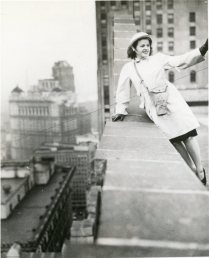 """Leaning against a parapet of a downtown Detroit office building, Miss Elizabeth Lakeman, a member of the nation's only OCD women fire watcher unit, signals a companion after she has discovered a simulated bomb burning on the roof of a nearby building."" Date Taken: 1942 (Local ID: 171-OCD-111-C)"