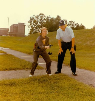 """At the FBI Academy, Quantico, VA, a special agent trainee receives instructions on natural point shooting for a FBI firearms instructor."" Date Taken: February 1976 (Local ID: 65-QT-9-9)"