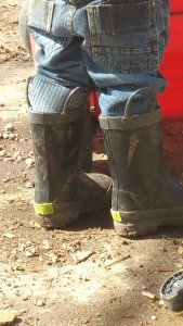Toddler in muddy rain boots