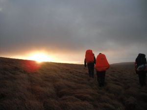 Immy and a friend walking hiking with backpacks with rain covers on towards the rising sun.