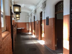 Into the room of cells with four doors leading into the cells on the right and sun shining through the windows in front