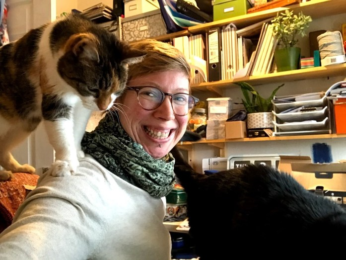 Me at my desk covered in cats sharing a bit of at home with the urban wanderer