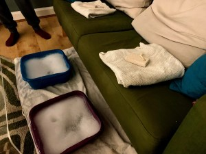 A scene set out like a really cheap spa. There are two washing up bowls set to the left of a settee. On the settee are two slightly grubby white towels with pummice stones placed on top of them. The washing up bowls are set on another grubby white towel on the floor and filled with bubble bath.