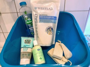 A washing up bowl with a bottle of Radox bubble bath, a packet of bath salts, a tube of foot exfoliator cream and a bottle of foot moisturiser. There are three pumice stones to the right of the bowl.