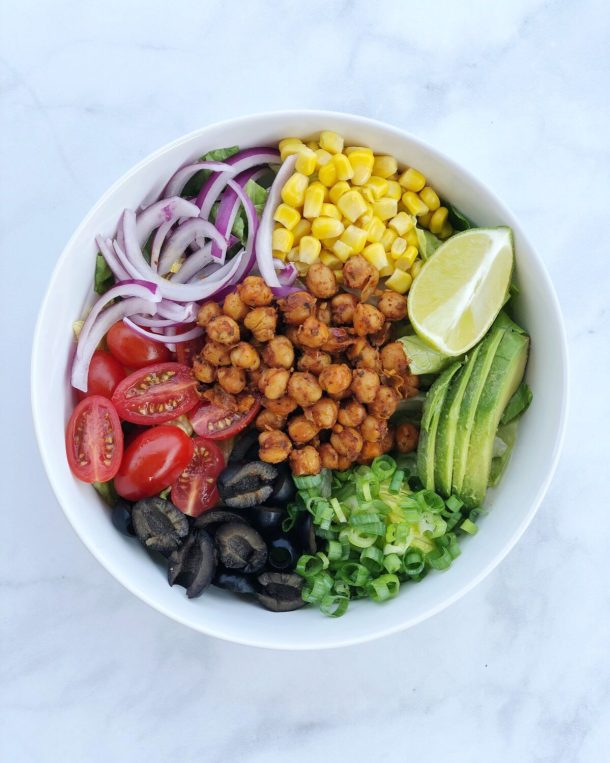 Chickpea Taco Salad is an easy vegan dish that comes together with seasoned garbanzo beans and your favorite taco toppings piled high on a bed of greens.
