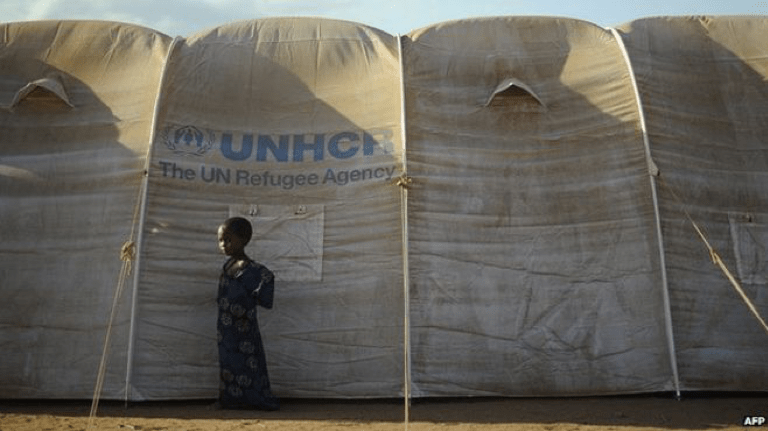 A child stands in front of a large tent that has printed on it the logo of UNHCR: The UN Refugee Agency