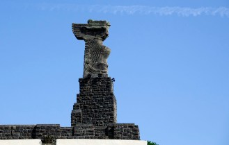 A statue of Nike of Samothrace by Vitorio Macho crowns the monument. It is inspired by the figureeads on the prows of ships and its head has been transplanted by that of Captain Elcano!