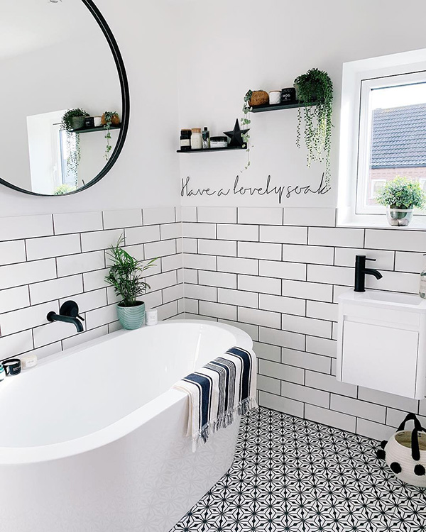 A small and modern bathroom with a bathtub and in black and white