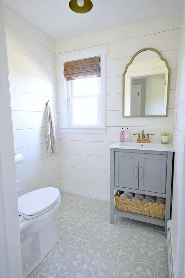 A small bathroom with whitewashed wood-clad walls