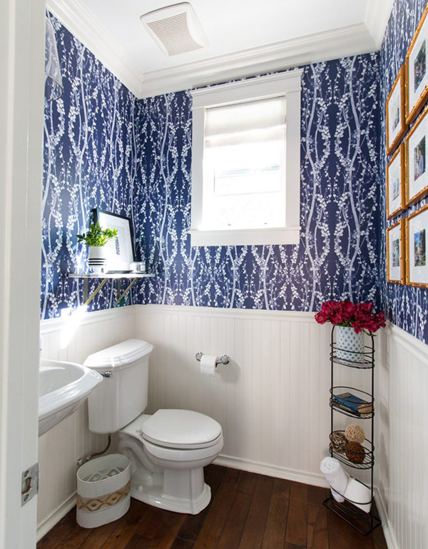 A small bathroom with blue wallpaper
